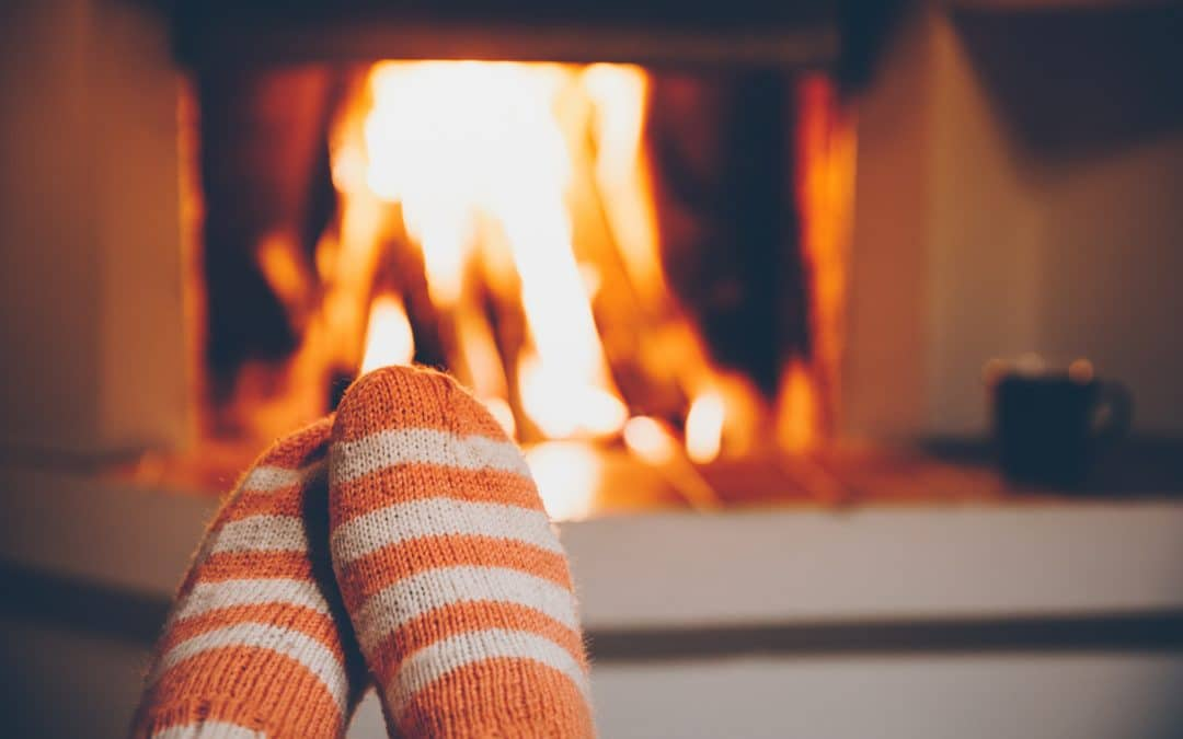 Feet in wool striped socks by the fireplace. Relaxing at Christmas fireplace on winter holiday evening.